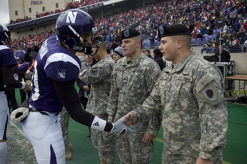 Sgt. Jordan Nechkash, Illinois Army National Guard, and Pfc. Giovanni Sciortino, Illinois Army National Guard, are congratulated by members of the Northwestern University football team. Nechkash and Sciortino participated as Northwestern University's honorary captains in honor of Veterans Day in Evanston, Ill., Nov. 8.