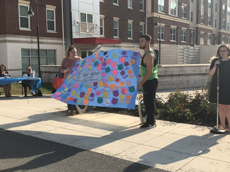 "Students Ashley Jacobs and Thomas Morrow hold a motivational poster containing positive notes including ""you are strong,"" ""you are brave"" and ""keep your head up"" to support domestic abuse survivors."