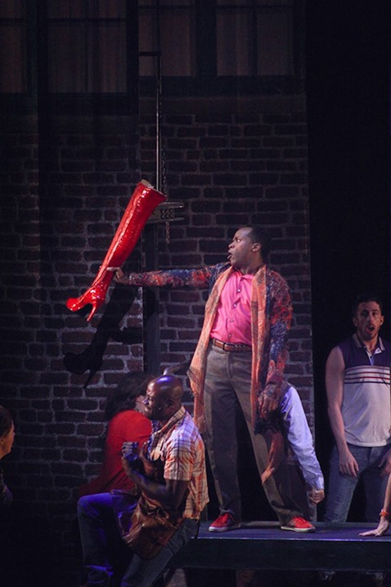 "Kenneth Mosley presents a ""kinky boot"" to commemorate the new boot business. Mosley plays Lola, a cross-dresser who designed the boots."