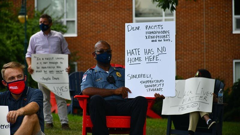 Lucas Everidge, left, and Shippensburg University Police Chief Michael Lee sit with signs outside the Dauphin Humanities Center Monday afternoon. Demonstrators gathered 6-feet apart in response to the use of a racial slur in Seavers Hall over the weekend. The demonstration was organized by students and faculty, and administration members, including President Laurie Carter, attended the event.