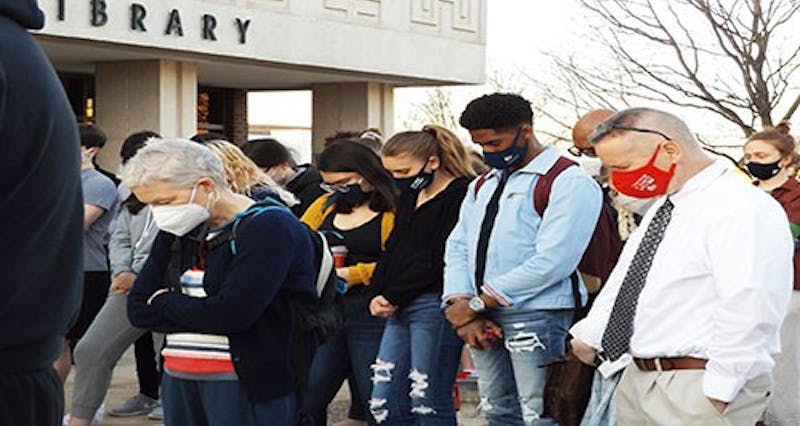 Attendees at the Act. Communicate. Teach Tolerance. Committee's vigil for the victims of the Atlanta, Georgia shootings, bow their heads in a moment of reflection.