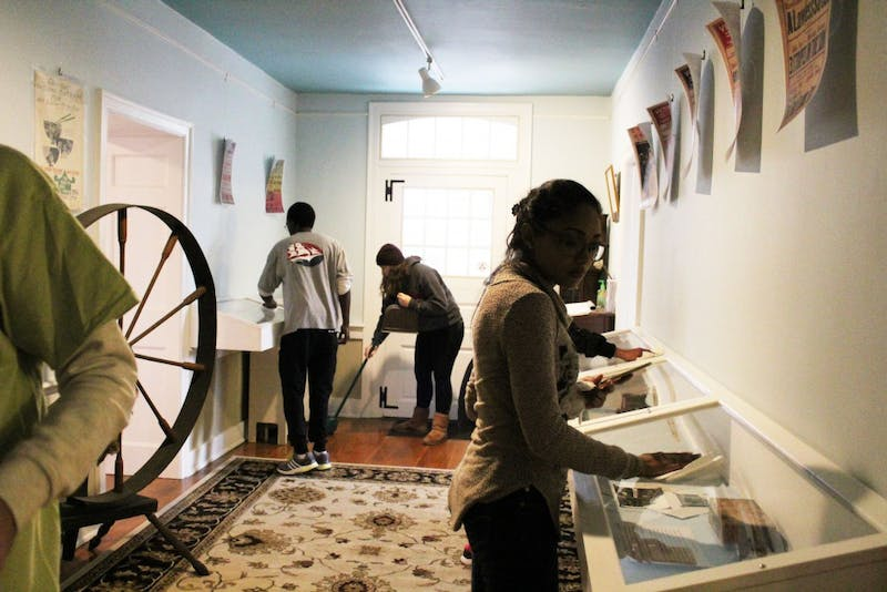 Students dust down the glass cases as well as sweep the floors inside of the Shippensburg Historical Society on Saturday.