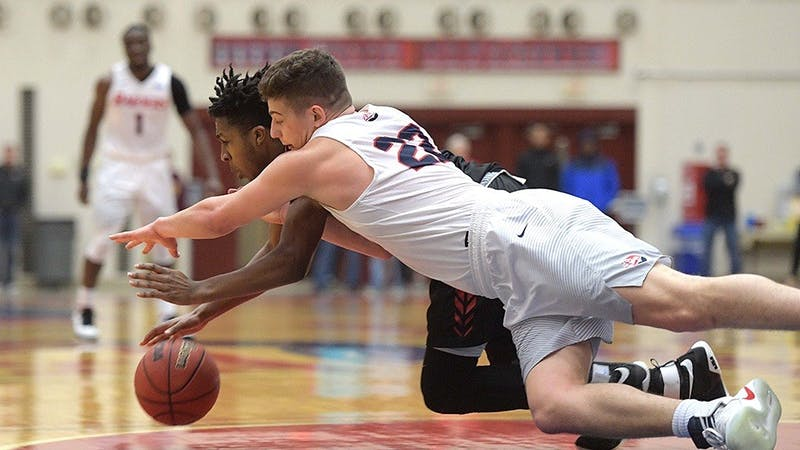 John Castello dives for a loose ball against East Stroudsburg. Castello scored 19 points in the Raider victory.
