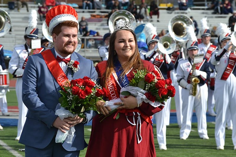 Tyler Rock and Bernie Schneider pose for photos after being announced homecoming king and queen during Saturday's football game. The homecoming court raised money for Hound Packs to benefit local students.