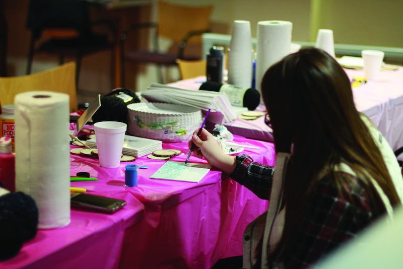 A Shippensburg University student paints on canvas during the SU Women's Center event.