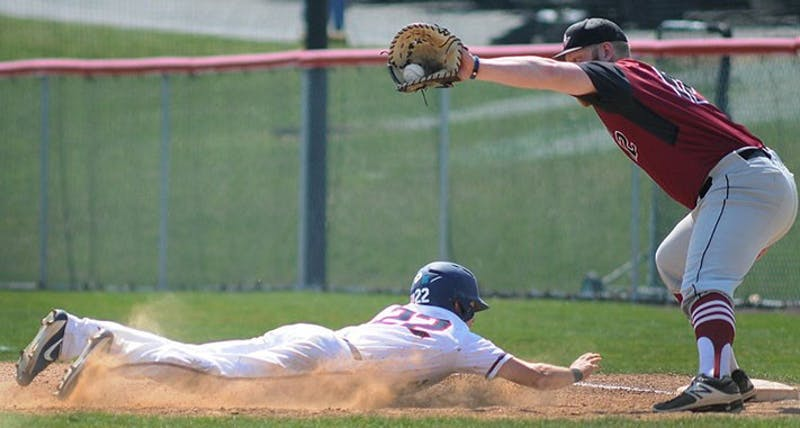 Second baseman Nick Spangler, left, slides back into first base after a pickoff attempt. Spangler recorded at least one hit in three of the Raiders' four games.