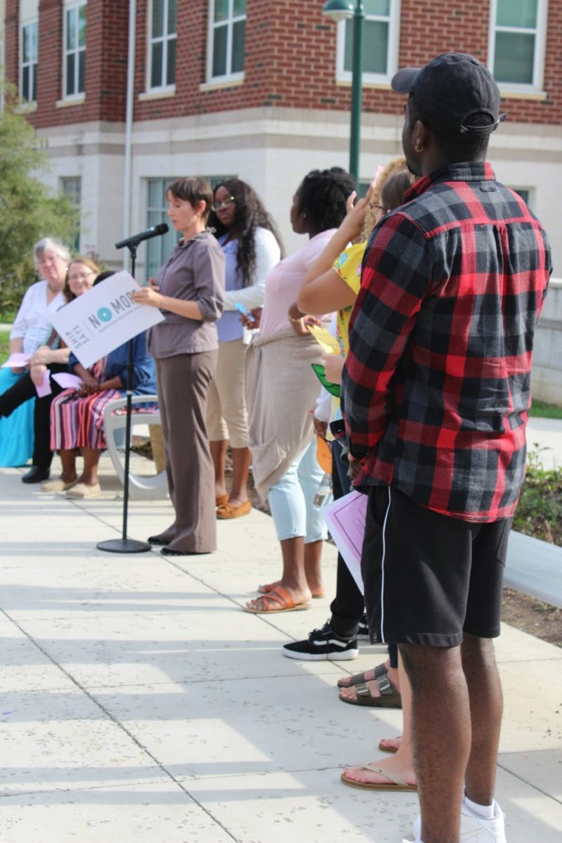 SU students line up to the right of Stephanie Erdice, director of the Women's Center, to read the inspirational messages they wrote on paper tulips to uplift and give hope to survivors of domestic violence and sexual assault.