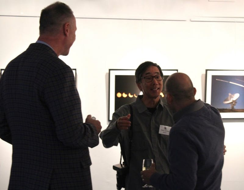 "Award-winning photographer Stan Honda mingles with Shippensburg residents during the opening reception of his ""STARLIGHT"" exhibit on Friday."