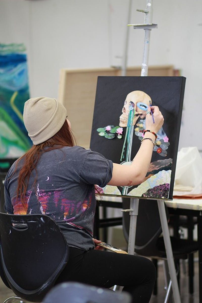 Senior art and design major Amanda Cruickshanks, who paints a picture above, is inspired by surrealist, abstract and expressionist art.