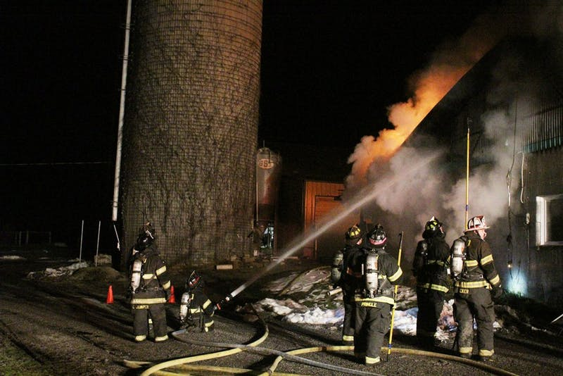 Flames shoot out of the barn as responders position themselves to tear open the panels of the building to douse the fire with water.