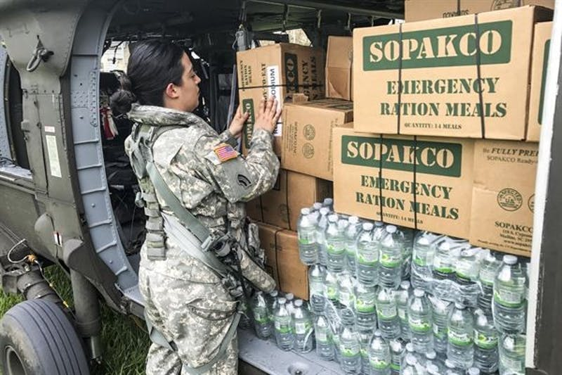 A member of Puerto Rico's National Guard packs boxes of ration meals to be sent to Puerto Rican families that were affected by Hurricane Maria.