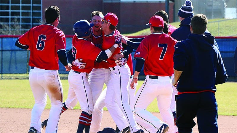 The SU baseball team celebrates with Cash Gladfelter (left) after he delivered a walk-off single in the third game of the series against Le Moyne.