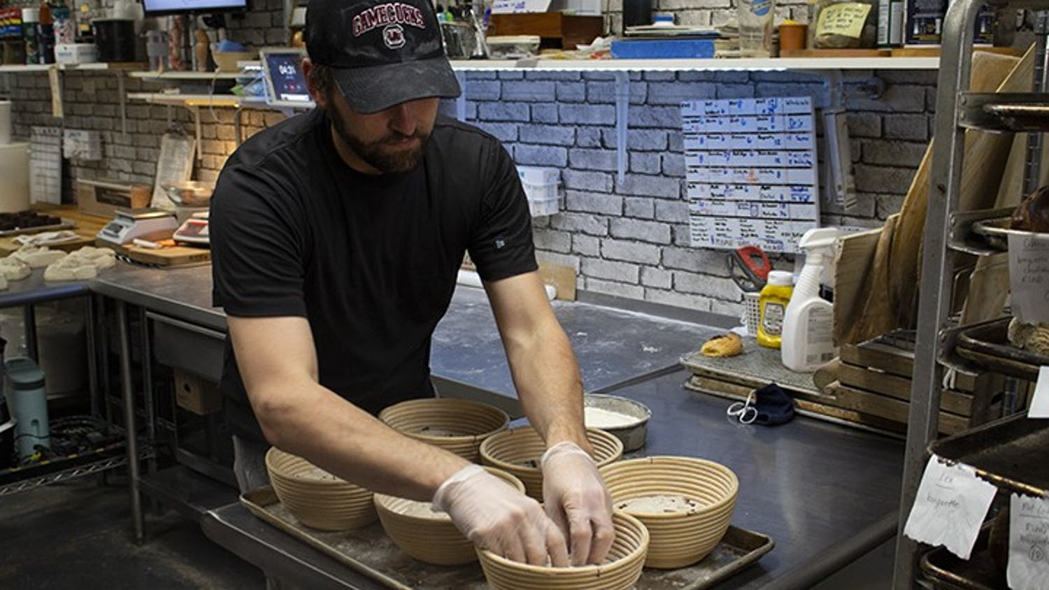 Owner of Crust Bakehouse Zackery Gates works in the kitchen to prep inventory.