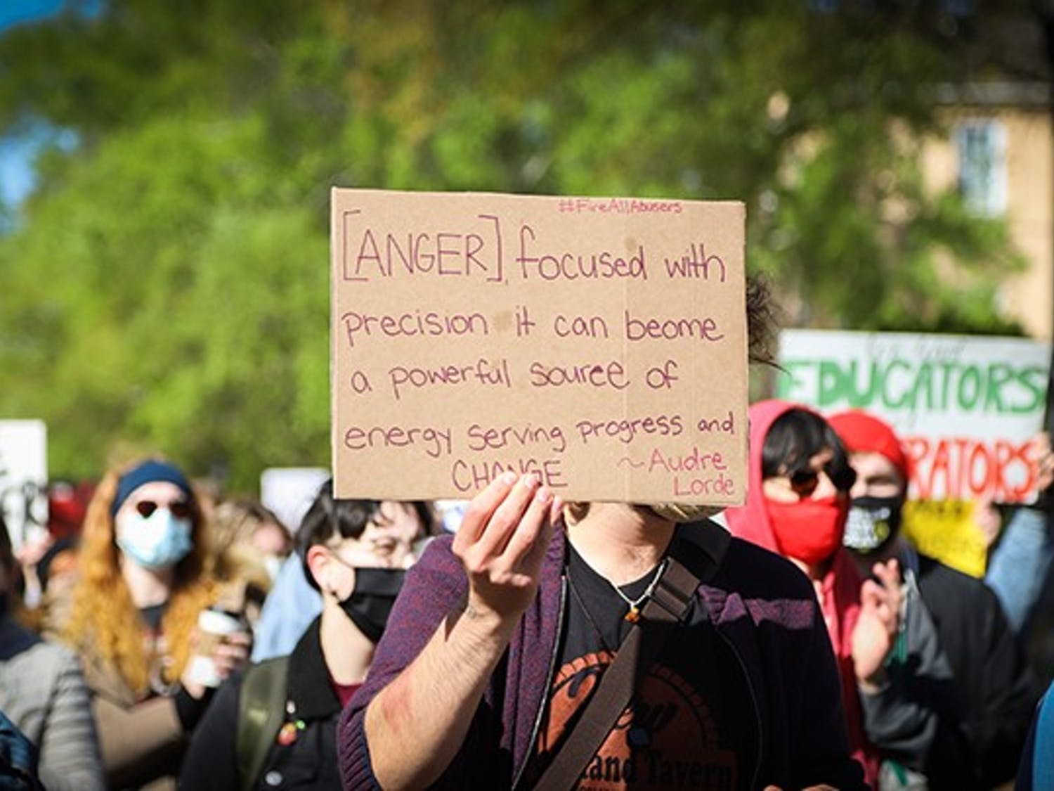 """A marching protest attendee holds a sign that has the quote """"[Anger], focused with precision it can become a powerful source of energy serving progress and change"""" by Audre Lorde written on it."""