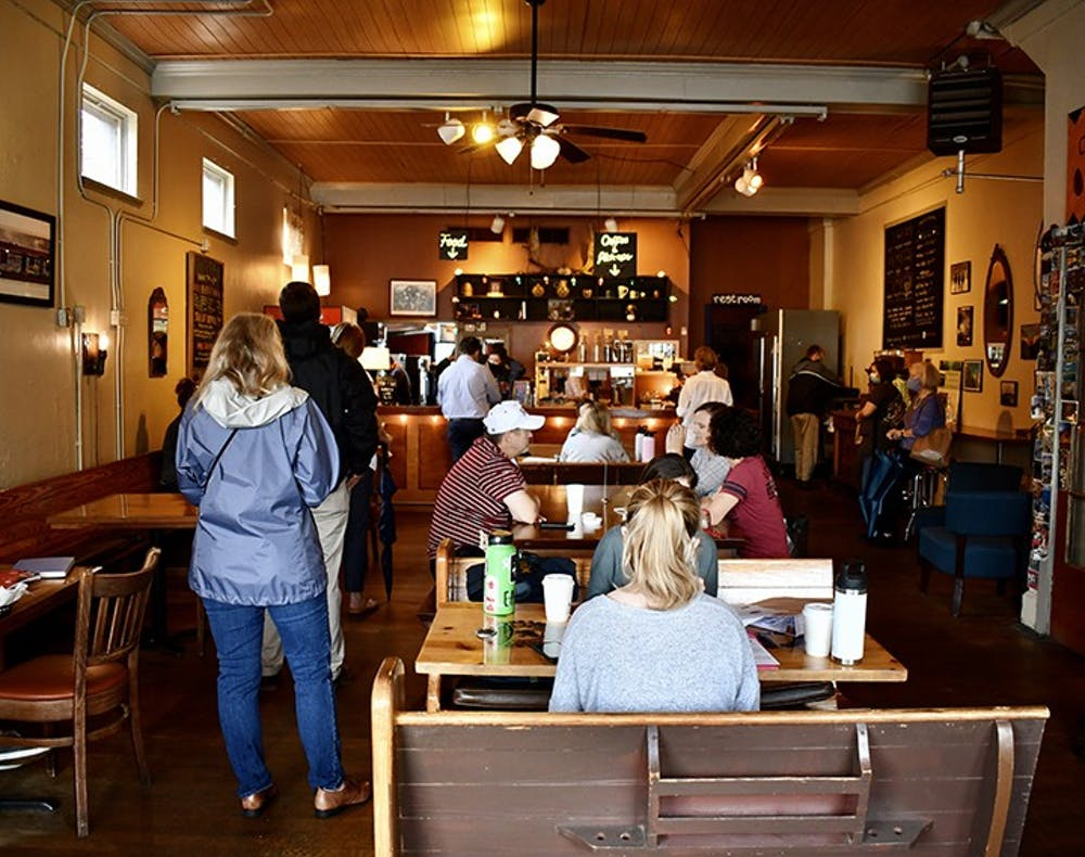 Customers wait in line for their order at Immaculate Consumption while other customers enjoy their orders in the provided seating.
