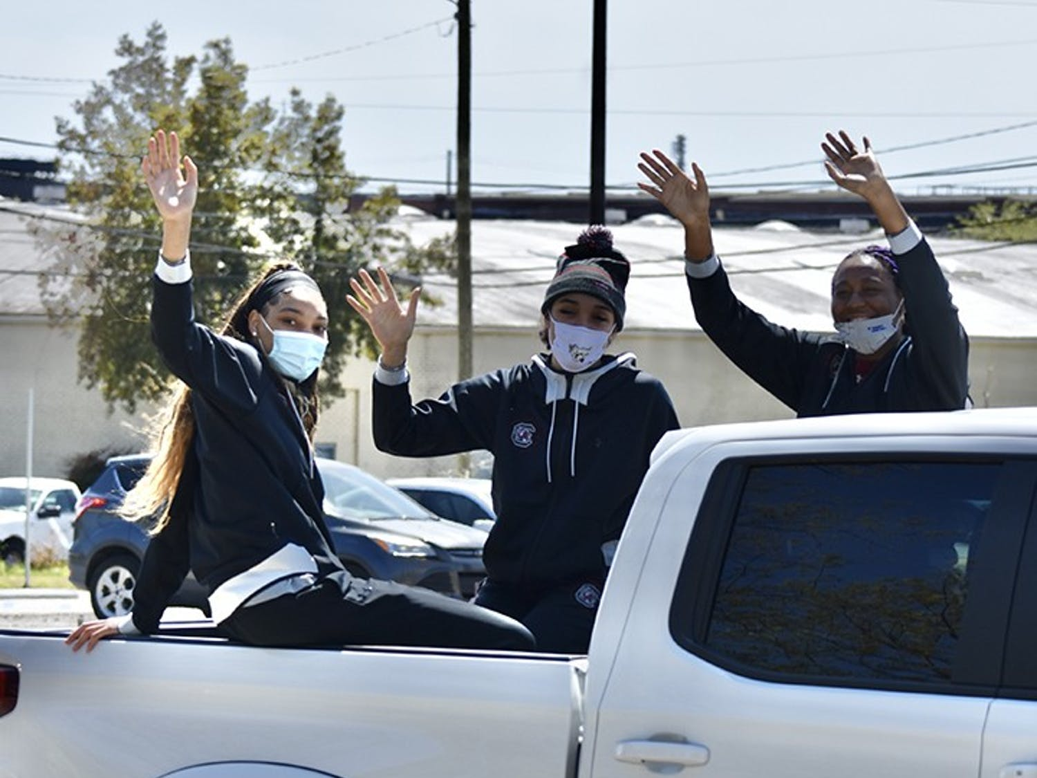 Junior forward Victaria Saxton, sophomore guard Brea Beal and sophomore forward Aliyah Boston wave at fans from the back of a truck that drove them in a procession-like fashion around the Colonial Life Arena parking lot.