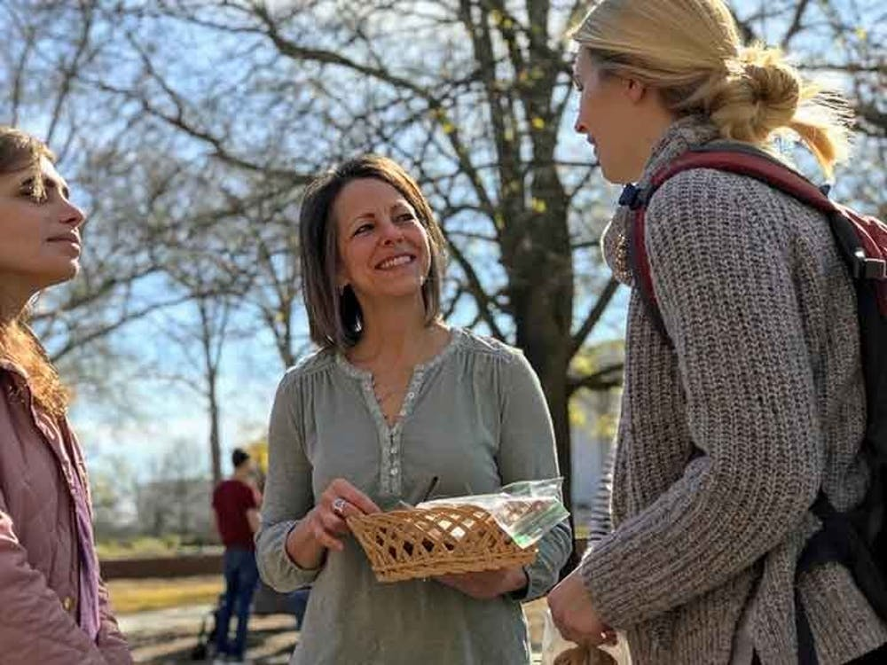 A student talks to an Ask a Mom member who holds a basket of cookies while in the clapping circle near Davis Field.