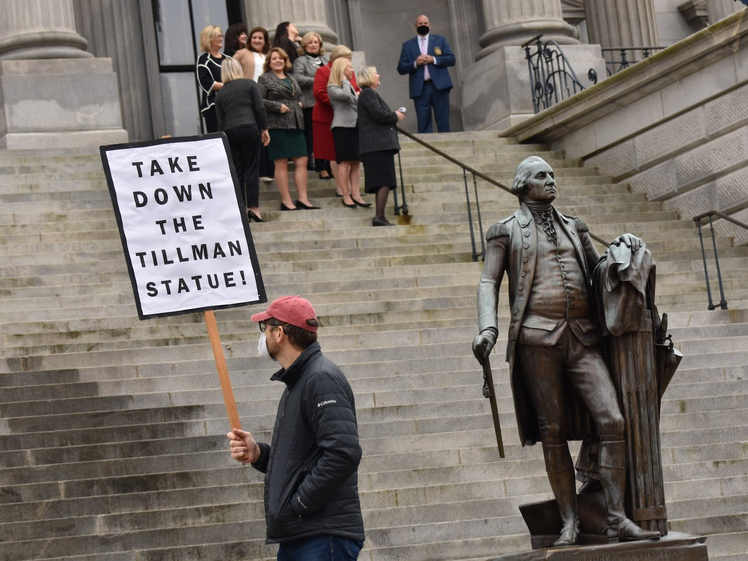 """A protestor holding a """"Take Down the Tillman Statue"""" sign walks in front of the South Carolina Statehouse while Statehouse workers observe."""
