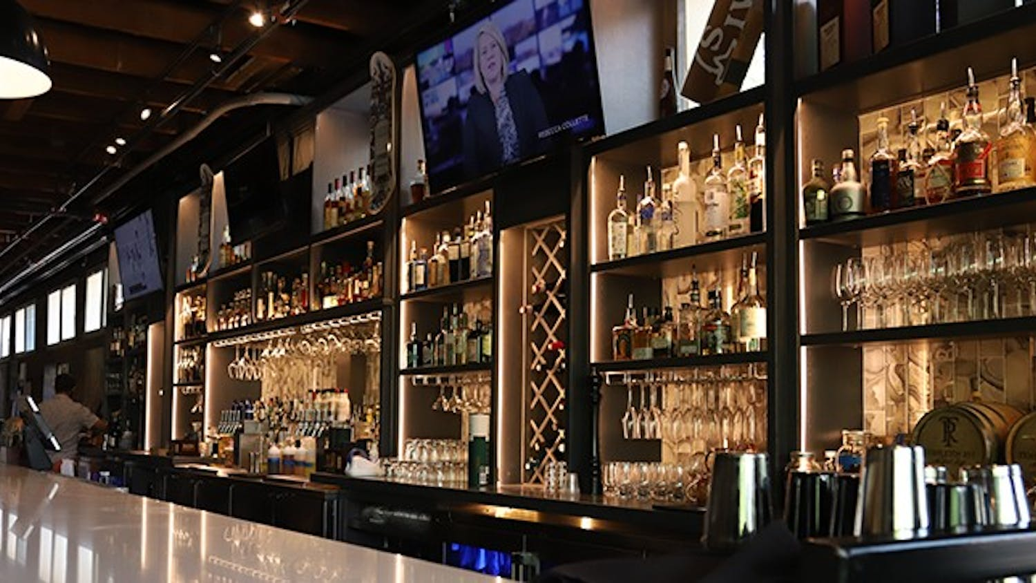 The bar inside Hendrix restaurant is stacked with different wines and liquors along with different glasses.