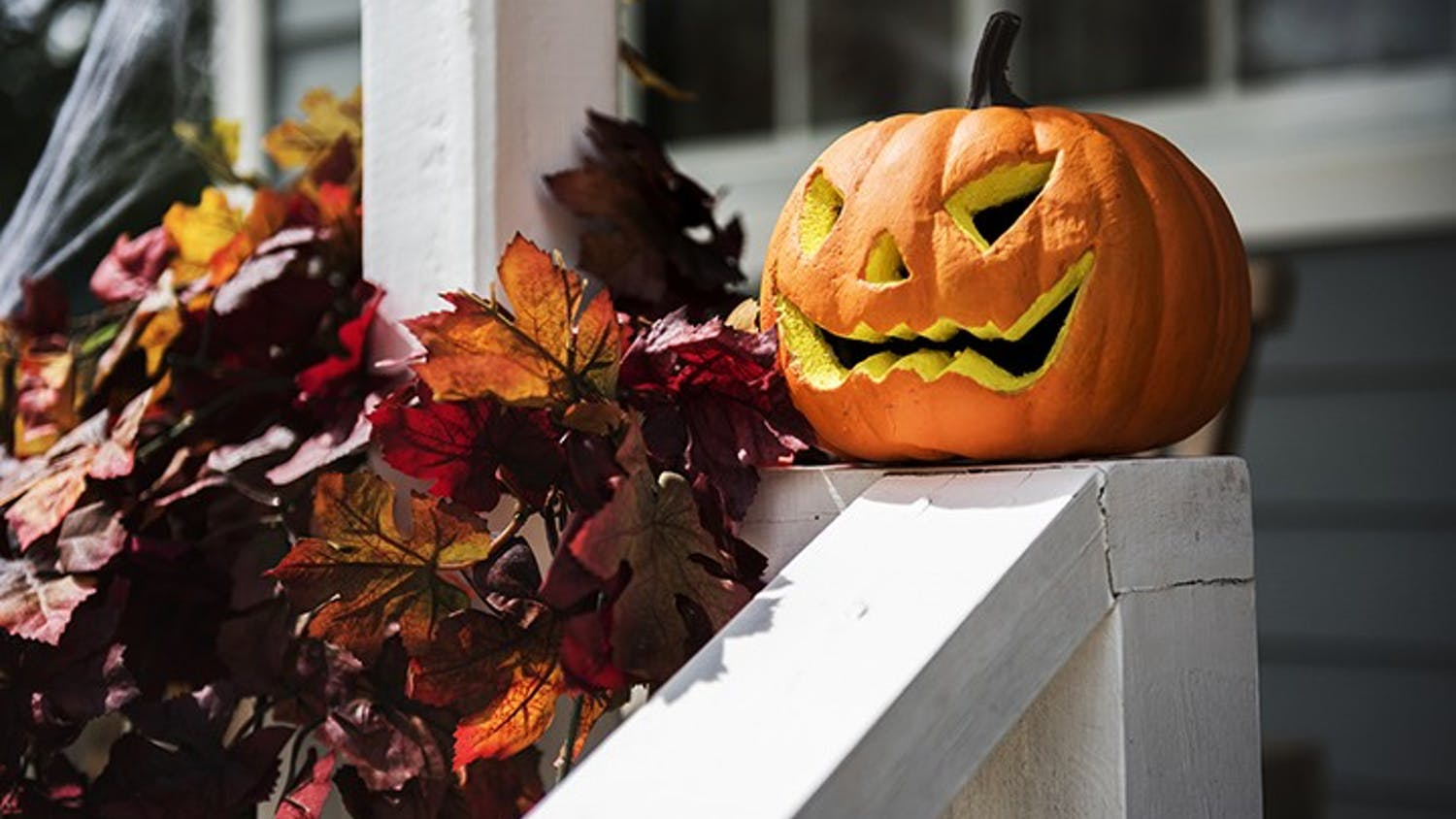 A jack-o'-lantern sits on top of a railing. Carving pumpkins into jack-o'-lanterns is often a popular fall activity.