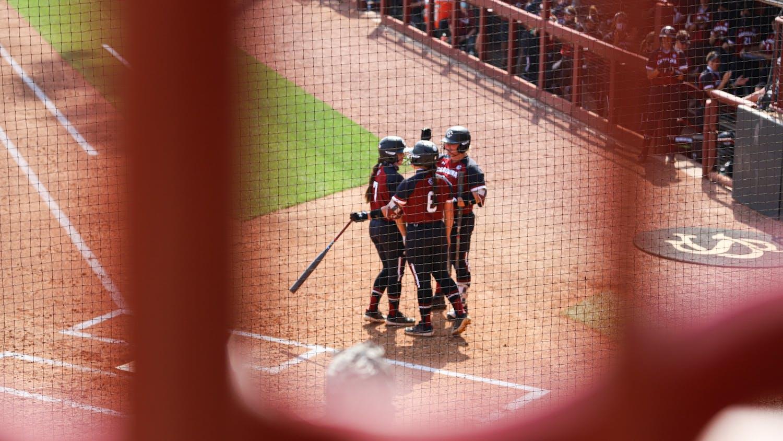 Members of the South Carolina softball team congratulate graduate student infielder Mackenzie Boesel after hitting a home run.