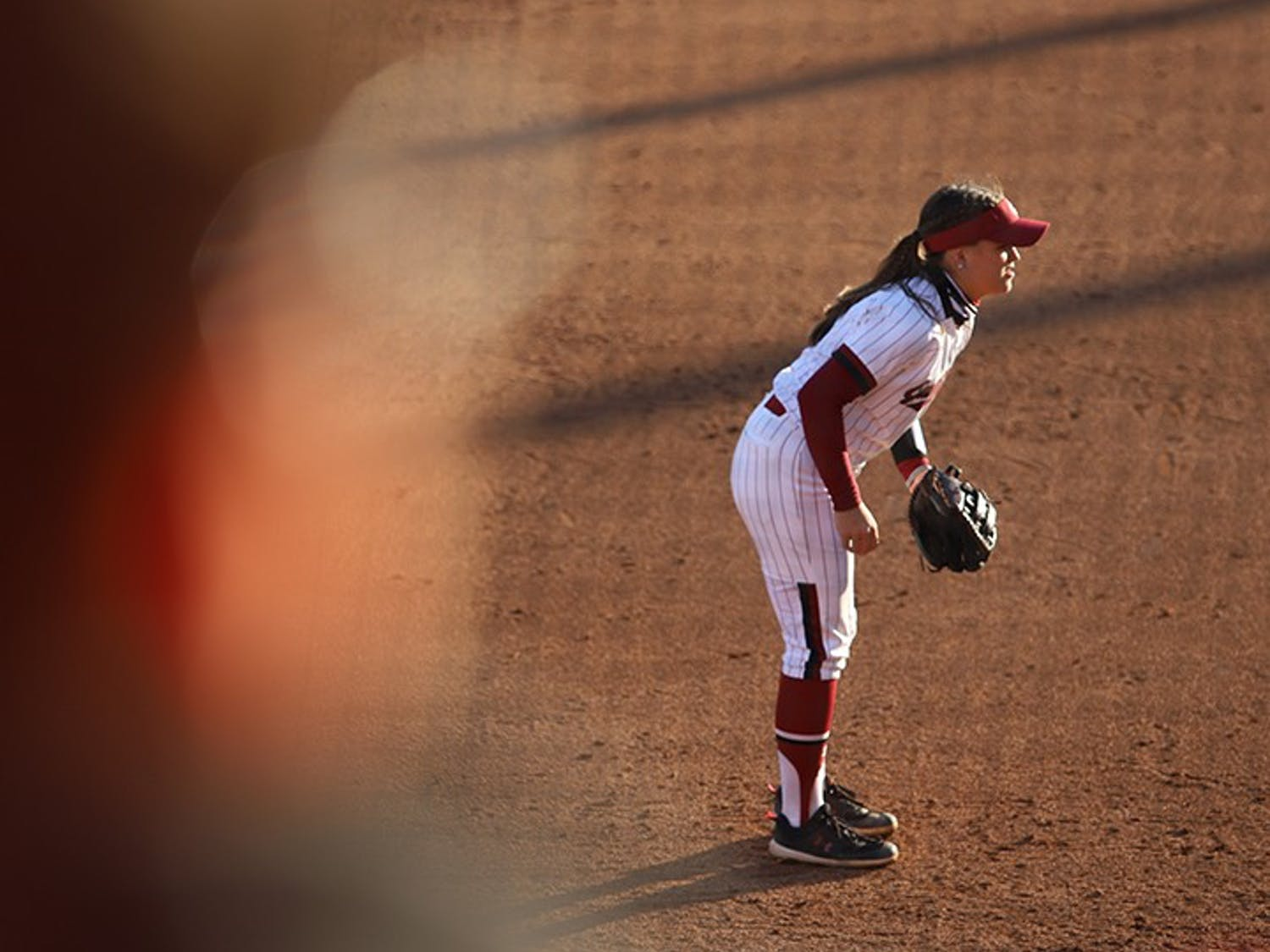Freshman infielder Maddie Gallagher watches the batter, ready to catch the ball, while her teammate prepares to pitch.
