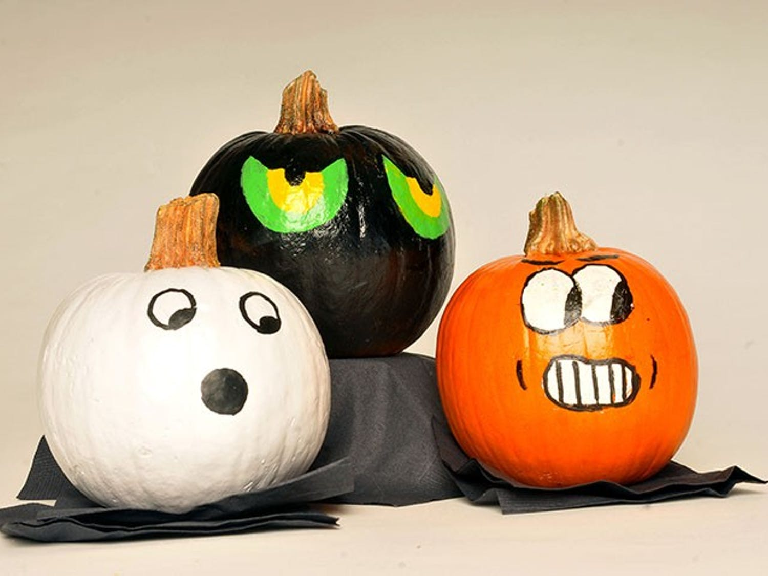 A set of three painted pumpkins on display. Painting a pumpkin is sometimes used as an alternative to carving it.