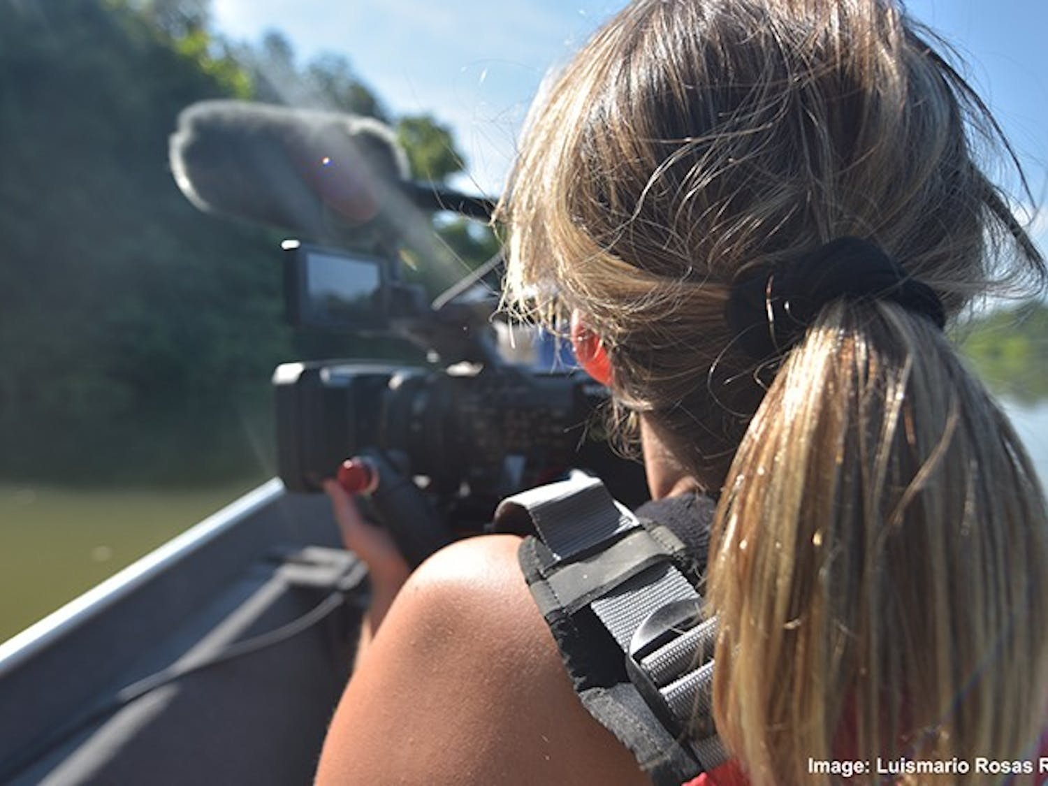 Emma Deloughry filming the Congaree River while sitting in a boat.