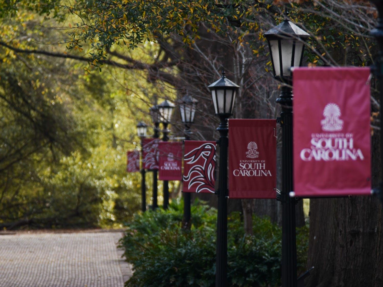 USC banners on lamp posts lining the Horseshoe at sunrise.