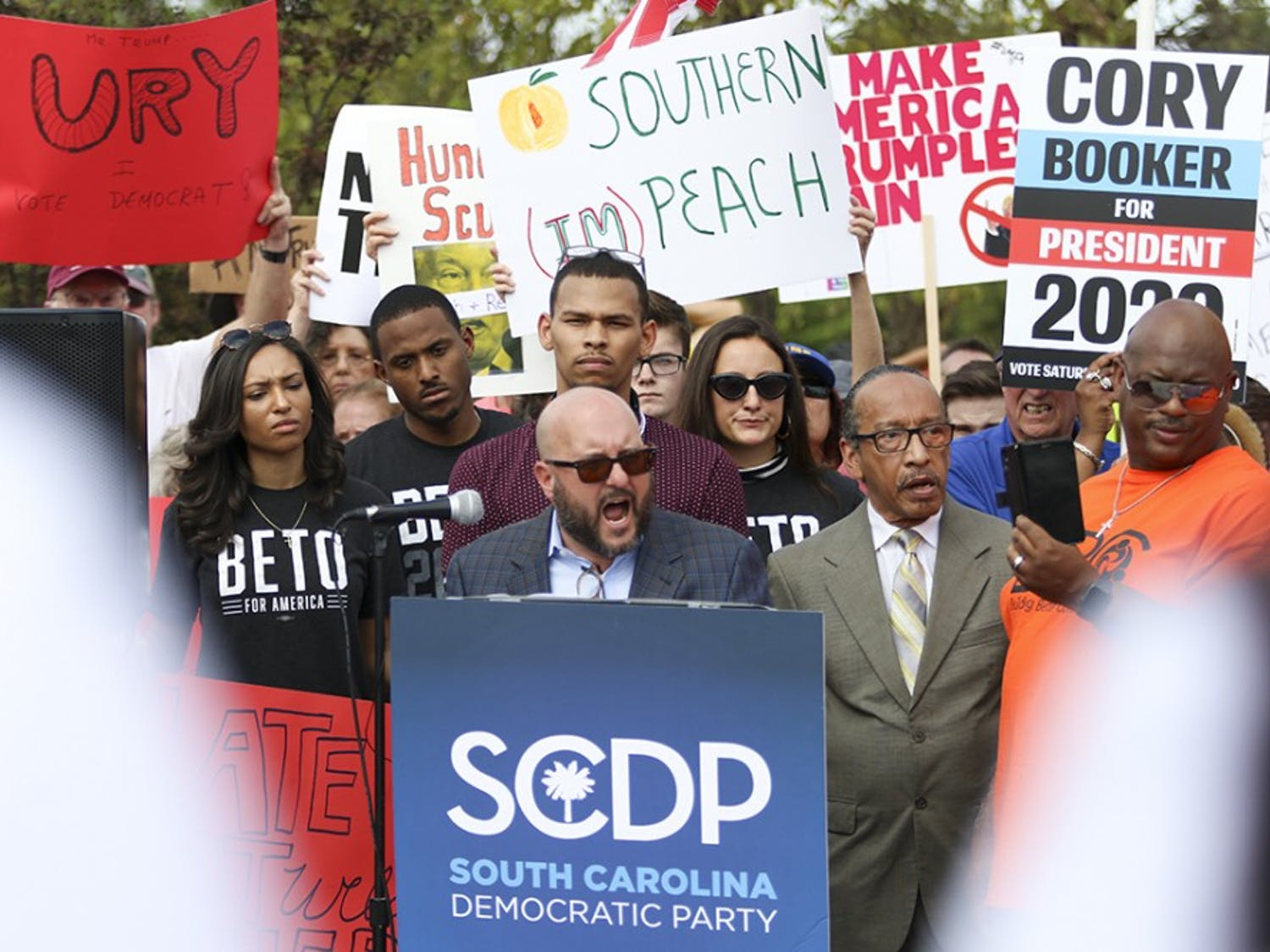 As speakers take the podium, a group of protestors gathered and chanted outside of Cory Booker's office on Oct. 25 while getting ready to march to Benedict College.