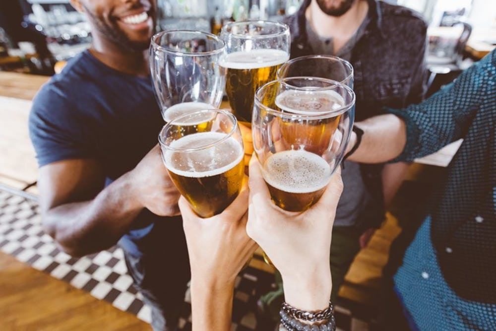 A group of people clink their glasses of beer together.