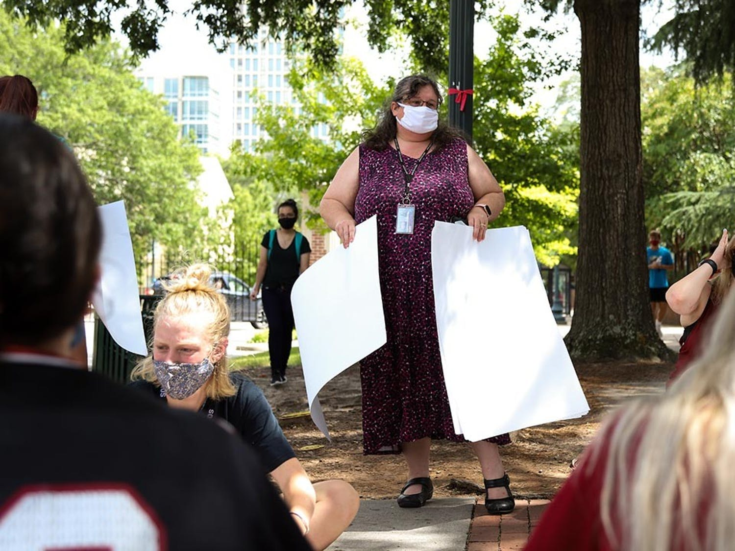 A staff member at the University of South Carolina hands out markers and paper to allow protesting students to make signs to combat Jim Gilles.