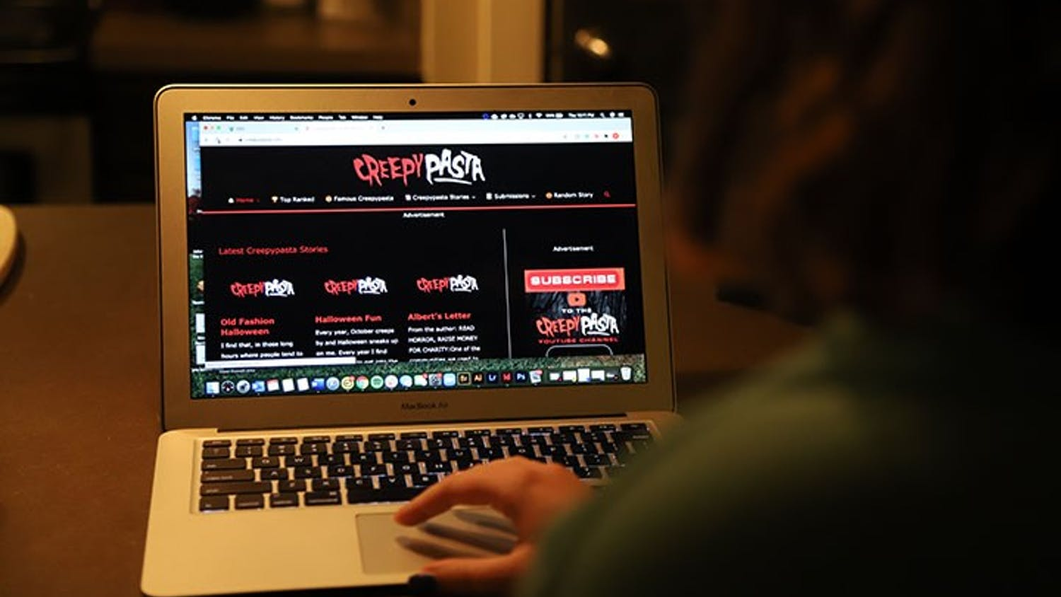 A person at a computer while it is displaying the Creepypasta website. Creepypasta is a horror story website where writers can post stories and receive feedback from their audience.