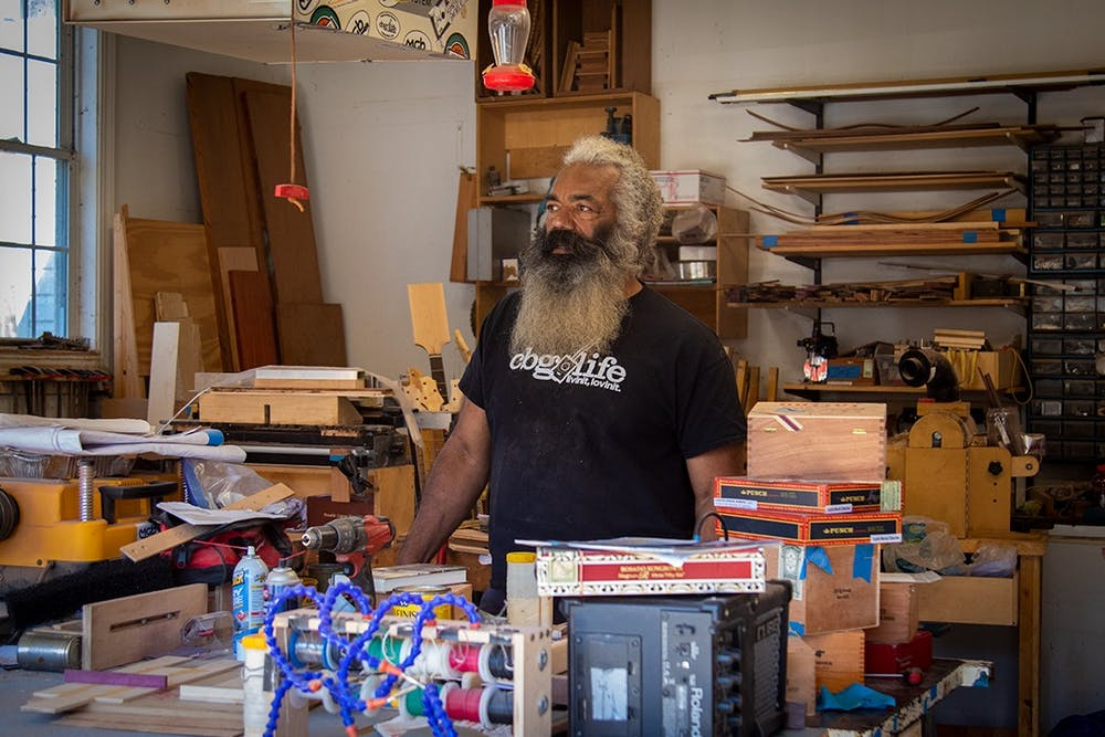 <p>Anthony Walker stands in the garage of his home behind his work bench. Walker currently makes cigar box guitars out of his home and sells them at Soda City market March through December.&nbsp;</p>