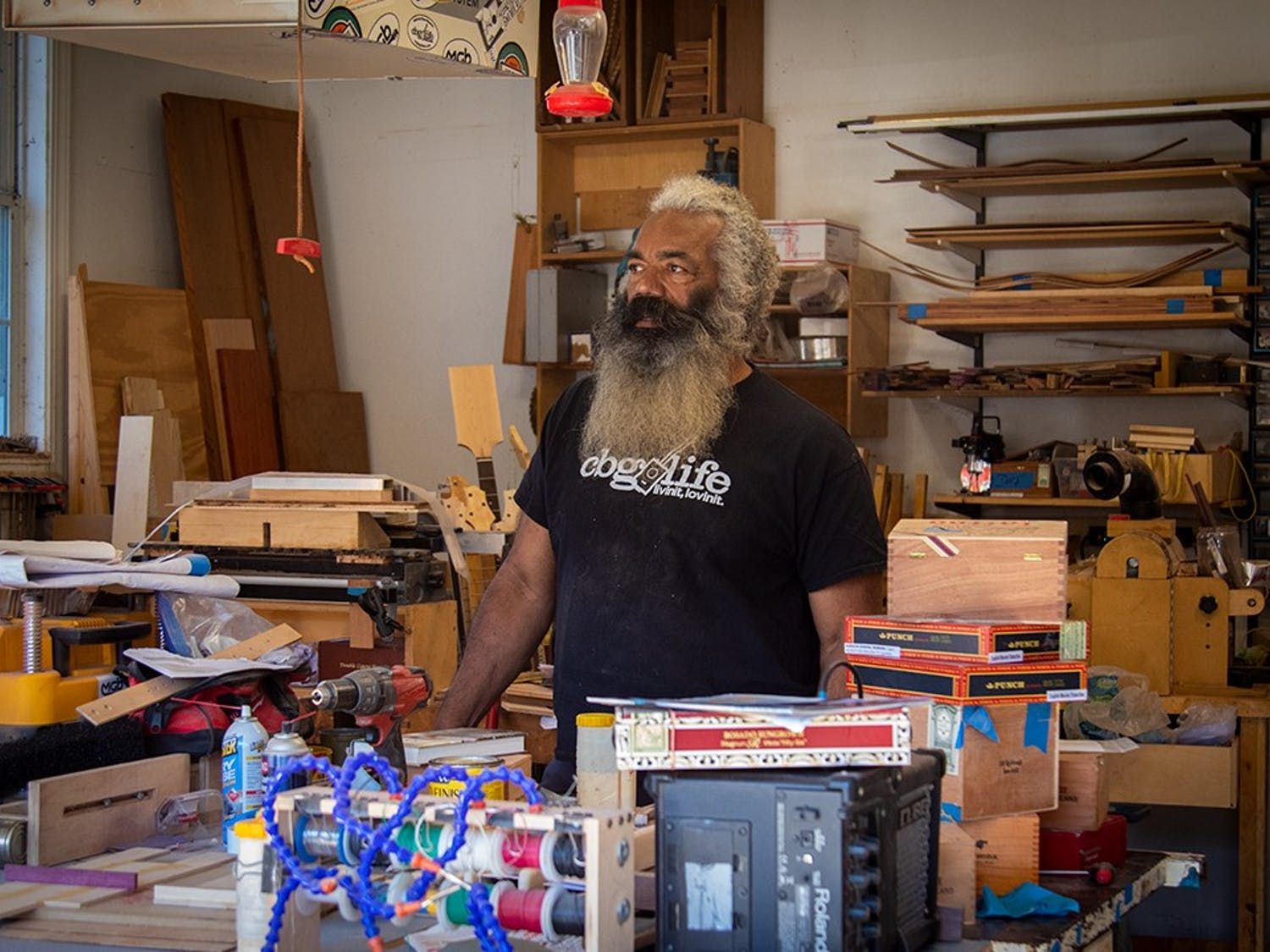 Anthony Walker stands in the garage of his home behind his work bench. Walker currently makes cigar box guitars out of his home and sells them at Soda City market March through December.