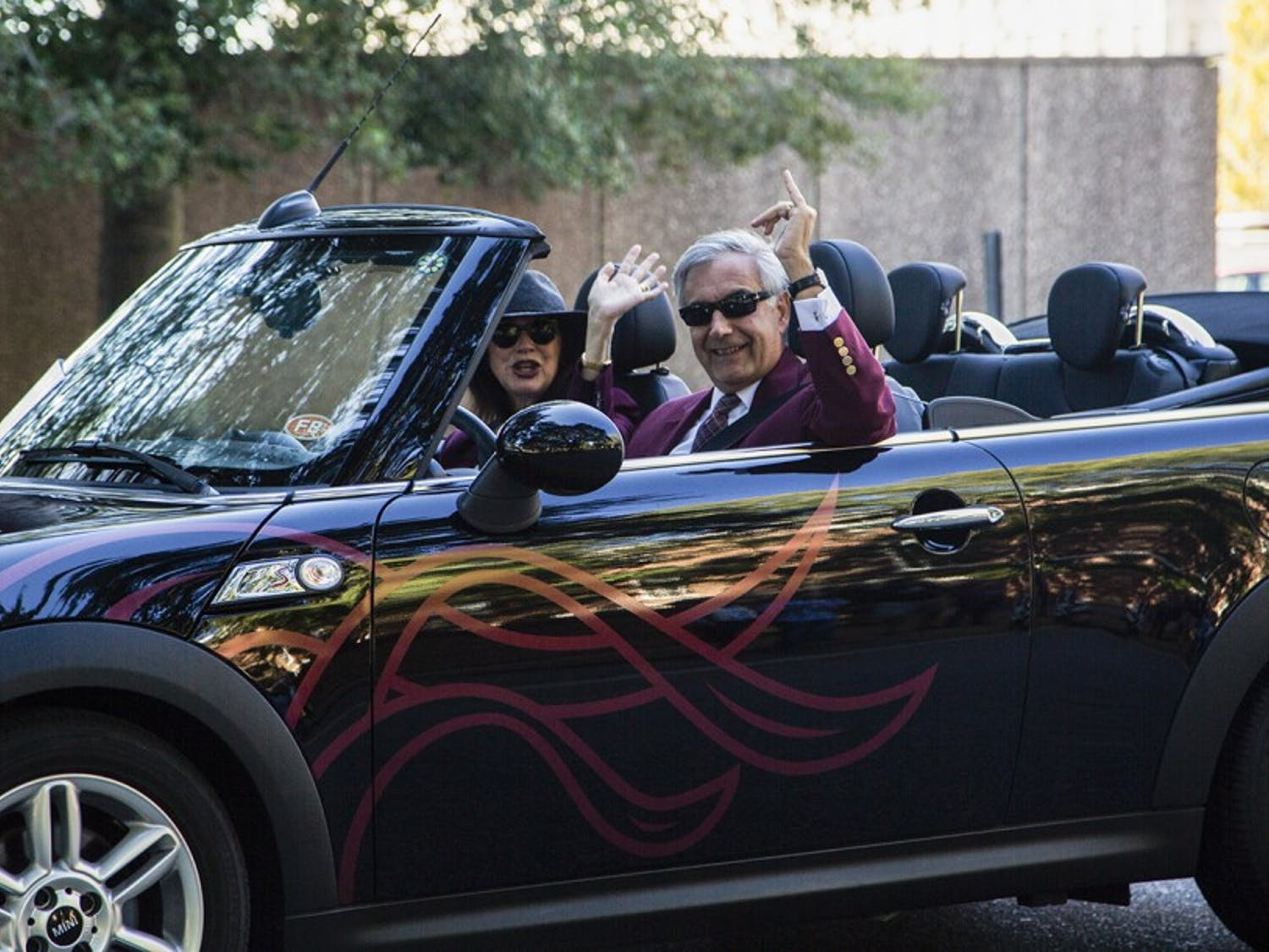 President Emeritus Harris Pastides and his wife Patricia Moore-Pastides ride in a car in the 2017 Homecoming parade.