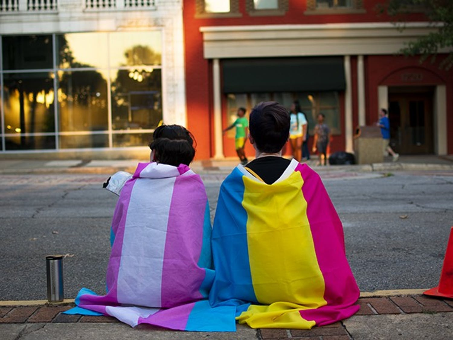 Two people, one wearing the transgender flag (left) and the other a pansexual flag (right), wait for the South Carolina pride parade to start this weekend.