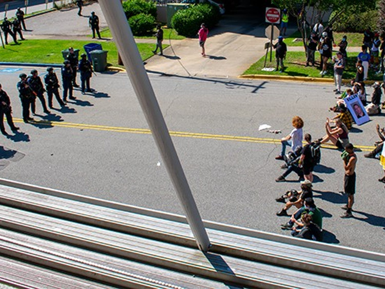 """Protesters kneel across from a line of armed police officers in front of the Columbia Municipal Court at the """"I Can't Breathe"""" protest on May 30."""