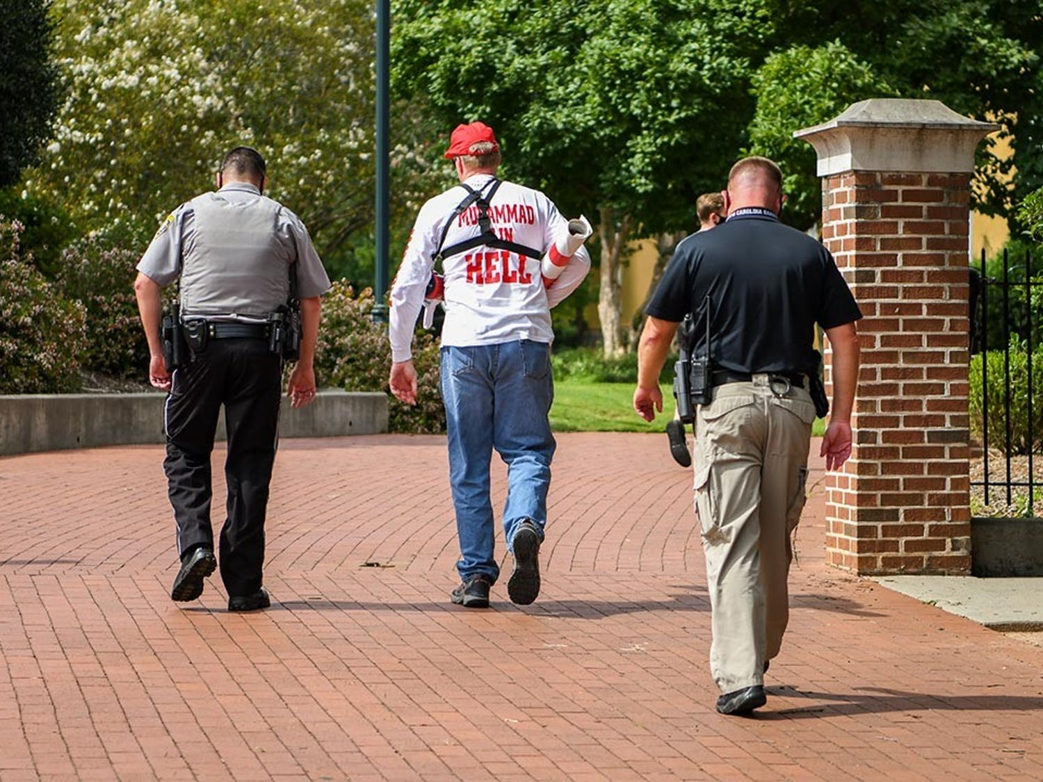 Jim Gilles walks away with a police escort after deciding to leave Greene Street Friday, Aug. 21. The students who were there cheered loudly as he left.