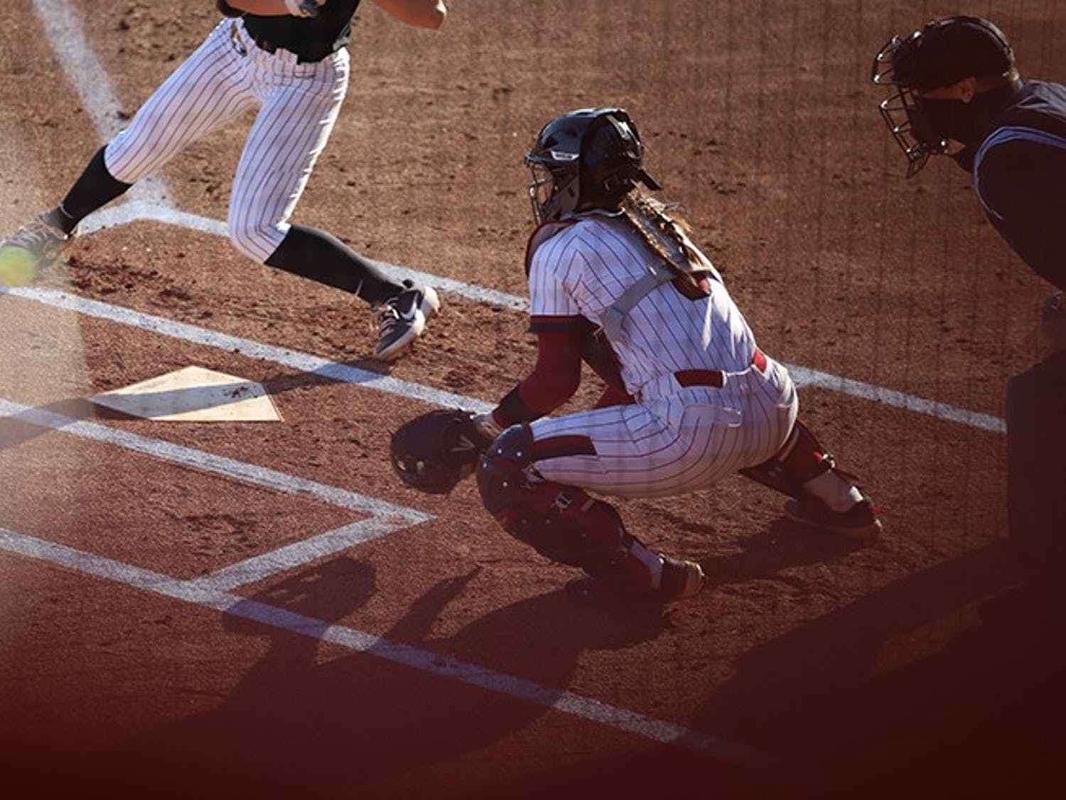 Junior catcher Jordan Fabian prepares to catch the ball while her teammate prepares to pitch.