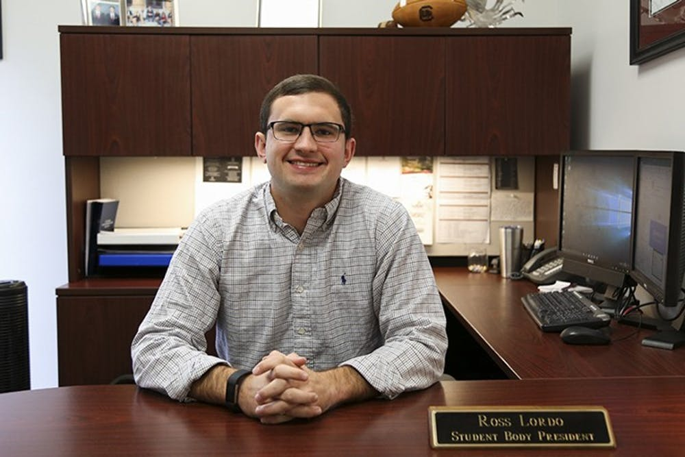 <p>Former Student Body President Ross Lordo sits at his desk while his name plaque is displayed. In his letter, Lordo reflected on athletic achievements, the Cockstock concert and Dance Marathon.</p>