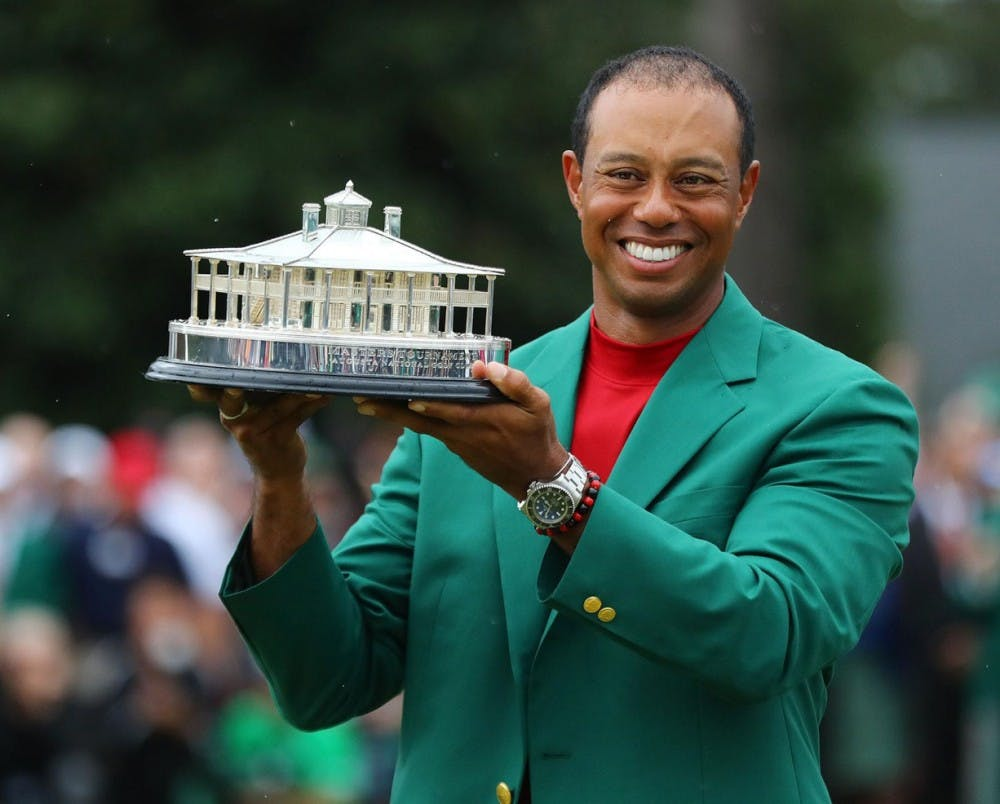 Wearing his new green jacket, Tiger Woods holds the trophy for winning The Masters at Augusta National Golf Club on Sunday. [Atlanta Journal-Constitution via TNS / Curtis Compton]
