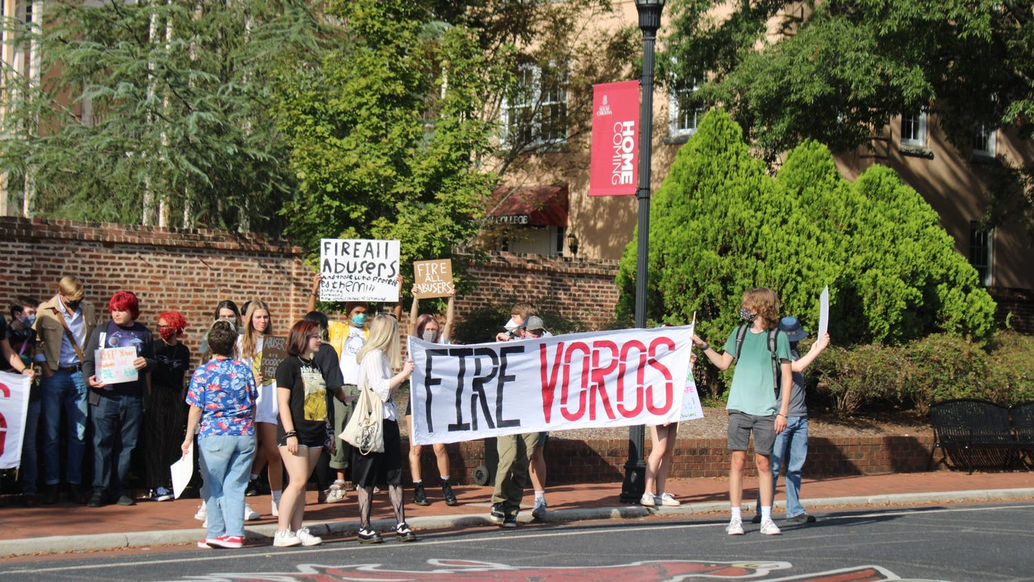 """USC Student protesters in front of Russell House on Greene Street in protest to fire Voros and others accused of sexual misconduct. Two people are holding a sign that said """"Fire Voros."""""""