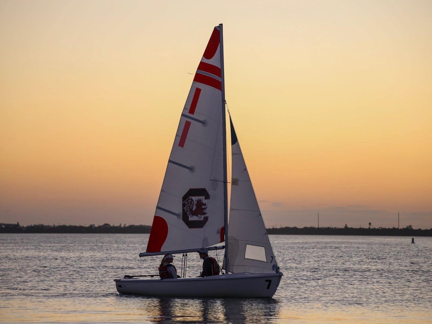 Two members of the sailing club sit on one of the sailboats during a sunset.