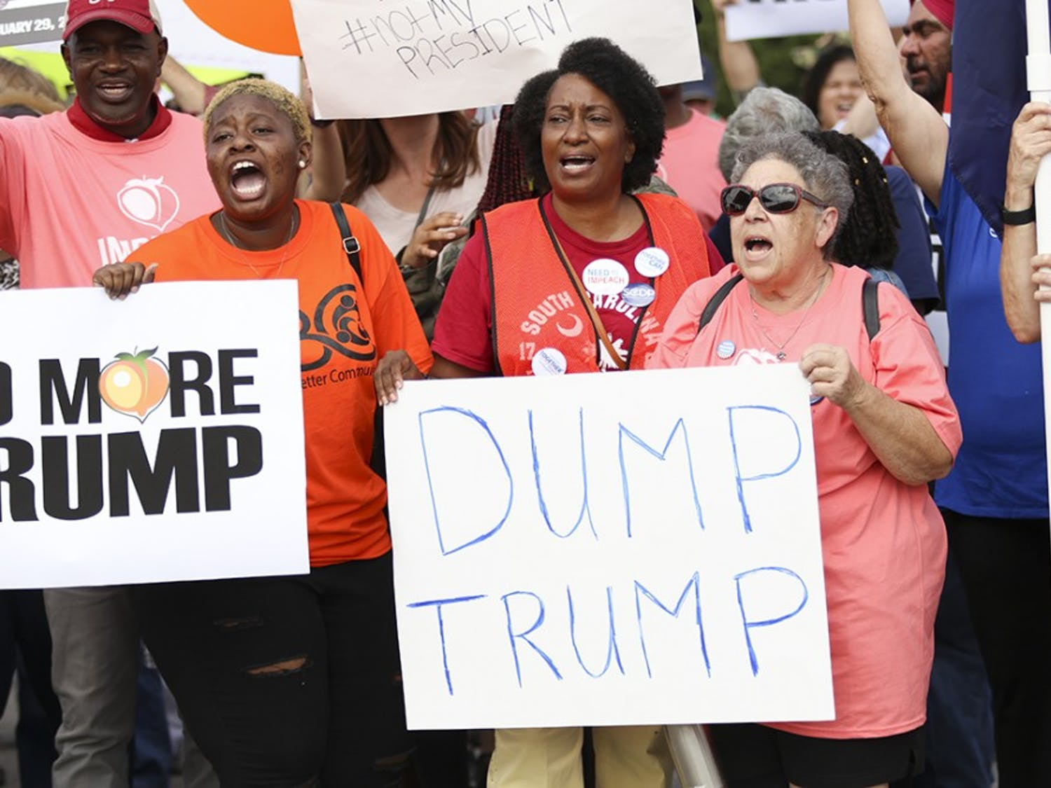 Non-Trump supporters chant and yell while holding protest posters on Oct. 25 before the march began to Benedict College.