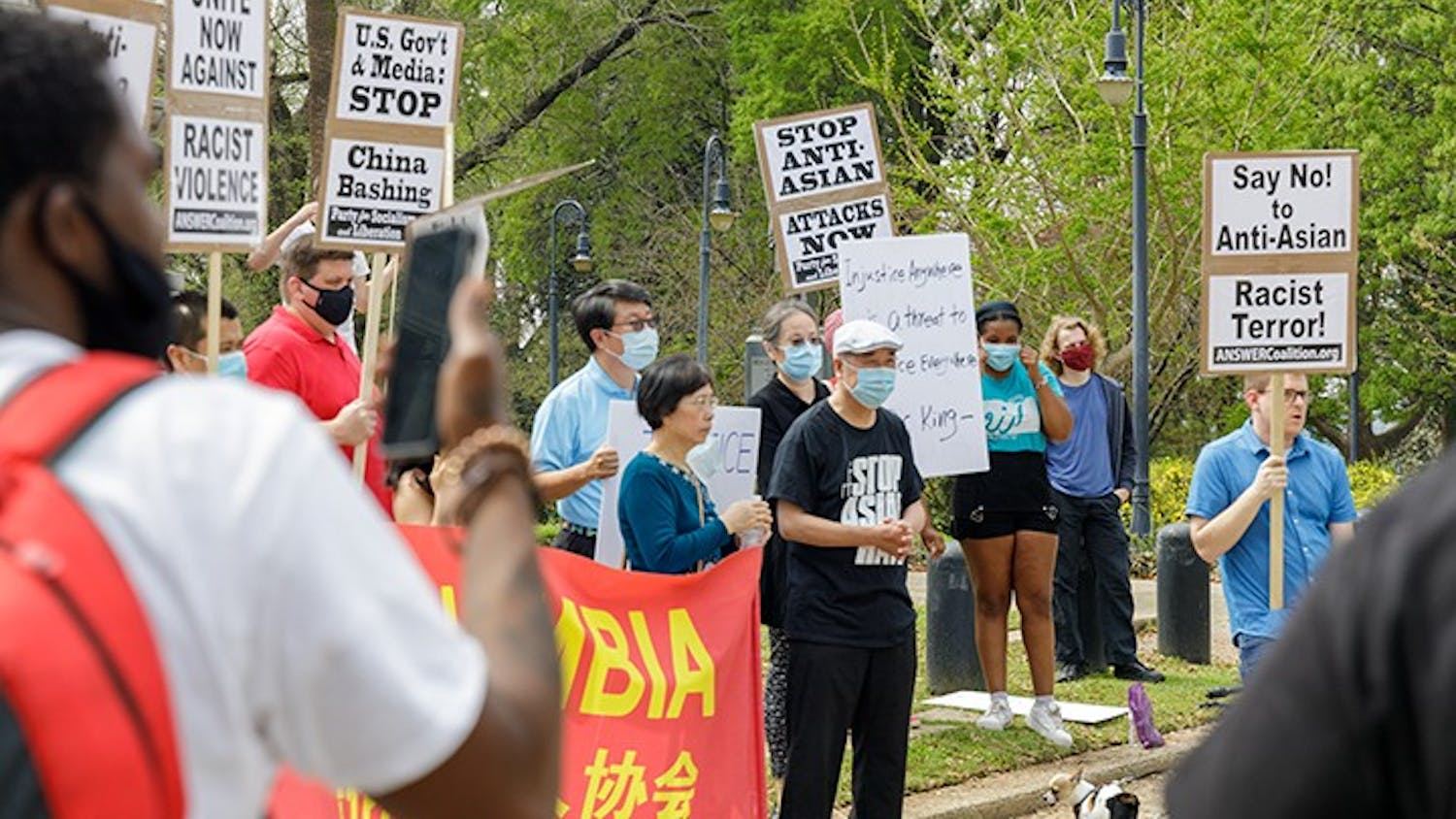 A group holds signs in protest of Asian hate that is happening within Asian communities.