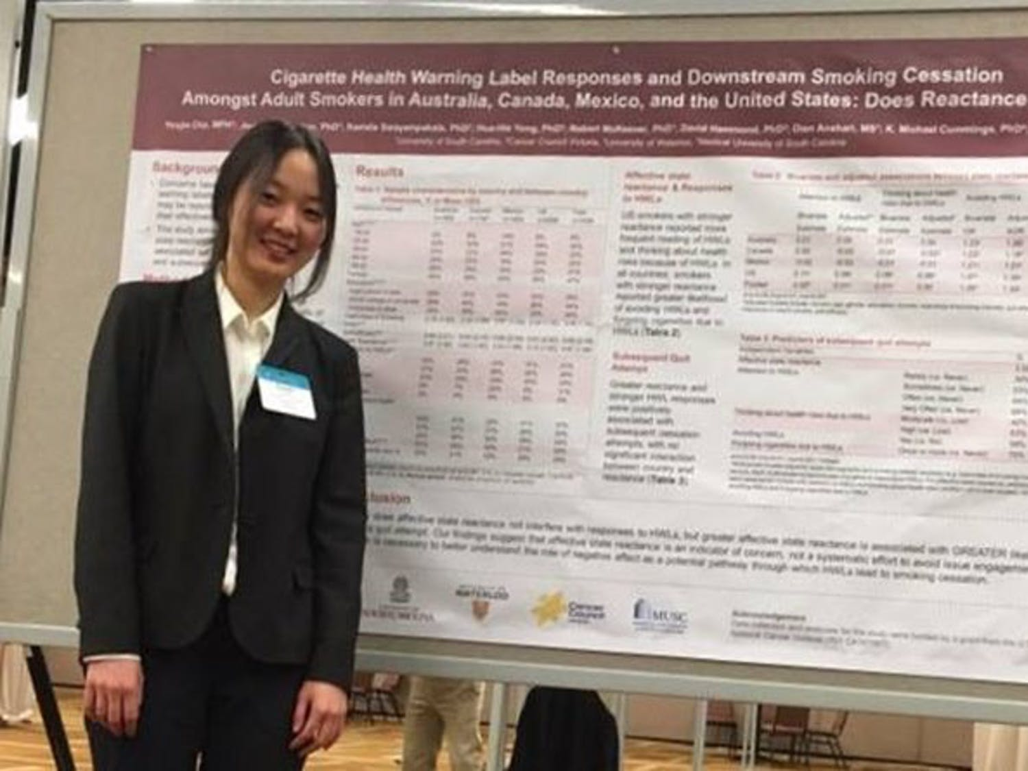 Yoojin Cho stands in front of her research presentation at the Society for Research on Nicotine and Tobacco conference.