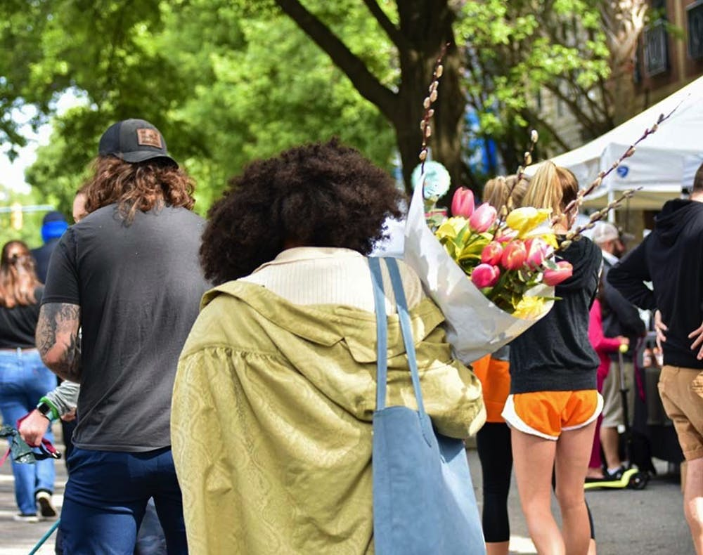 <p>A woman walking with a bouquet of tulips down Main Street through Soda City Market. Soda City is a marketplace where around 150 vendors and artists create a diverse and lively experience for the thousands who attend.</p>