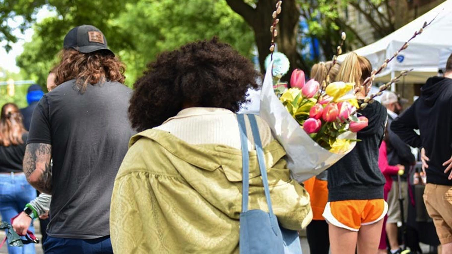 A woman walking with a bouquet of tulips down Main Street through Soda City Market. Soda City is a marketplace where around 150 vendors and artists create a diverse and lively experience for the thousands who attend.