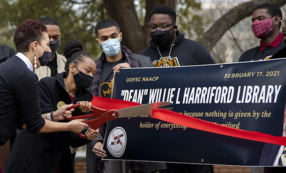 <p>NAACP Chapter president Caley Bright cuts the ribbon during the NAACP press conference.&nbsp;</p>